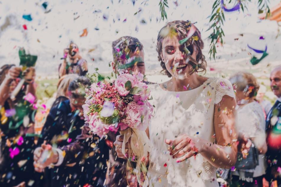 novios con confetti de colores a la salida de la ceremonia en una boda al aire libre