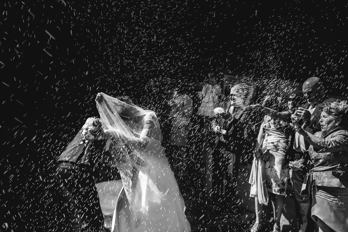 salida de los novios de la iglesia lanzándoles arroz fotografía en blanco y negro de bodas