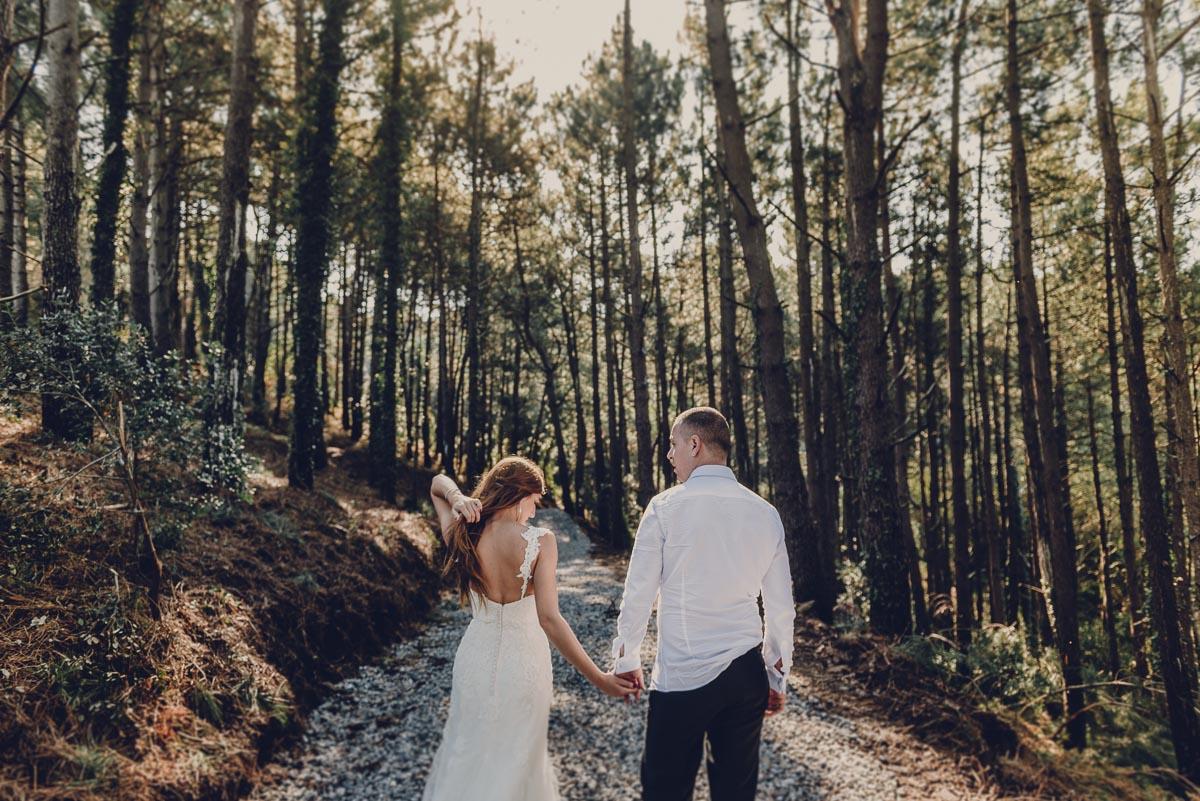 Novios en un bosque de pinos en Euskadi, la novia se está tocando el pelo y están de la mano