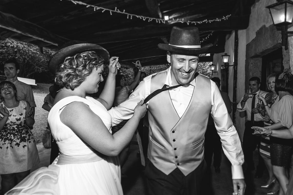 novios bailando en blanco y negro con un sombrero. La novia le está agarrando de la corbata