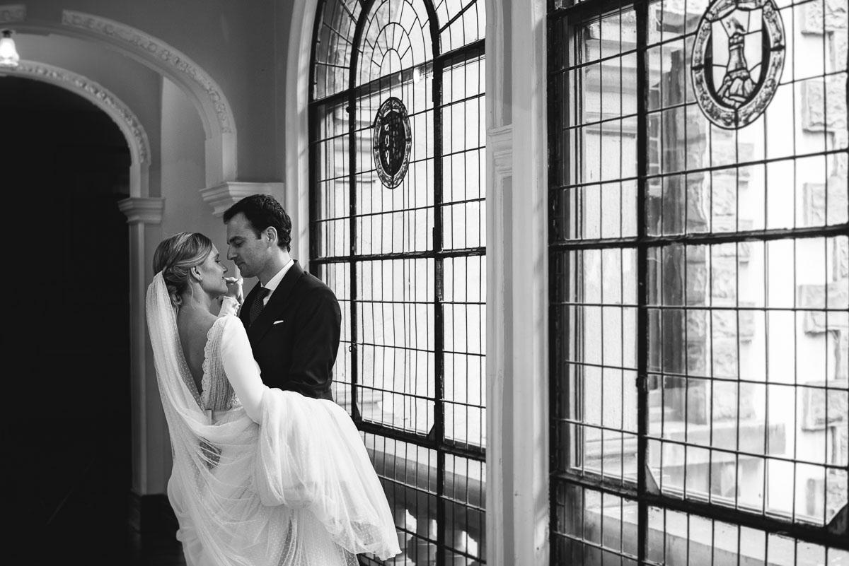 novios bailando en el san joseren, novia con velo y agarrados de la mano, fotografia muy romántica y novios mirándose. Fotografía en blanco y negro