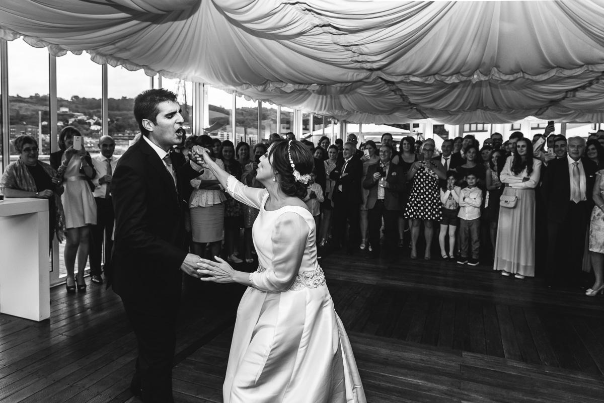 novios bailando  en un a boda delante de sus invitados, fotografía en blanco y nergro