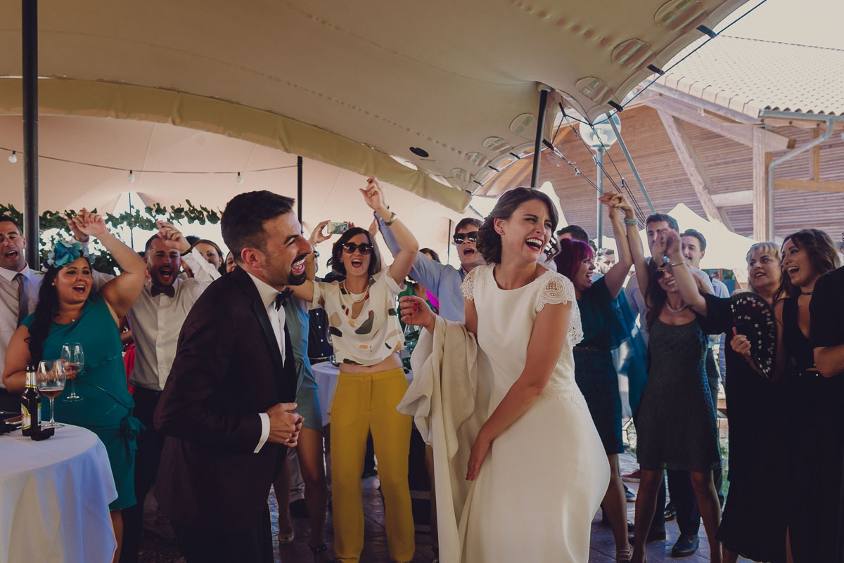 fotografia de novios felices en el coctel de su boda bailando, en la huuerta vieja, en Laguardia. Novia vestida de Alicia Rueda