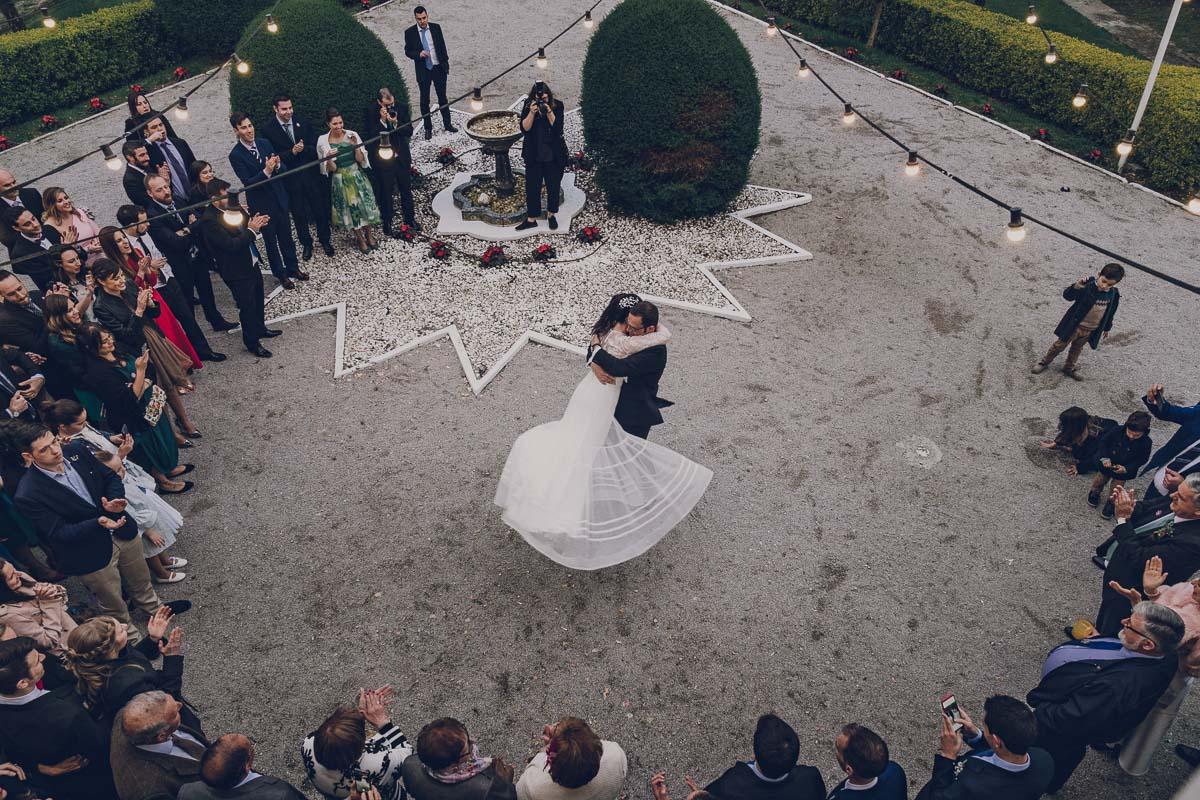 novios bailando al aire lubre su baile de bodas, el novio está cogiendo en el aire a la novia, la fotografía está sacada desde arriba, plano cenital