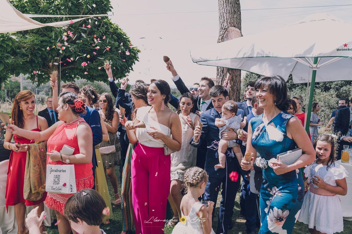 invitados lanzando arroz a los novios en una boda
