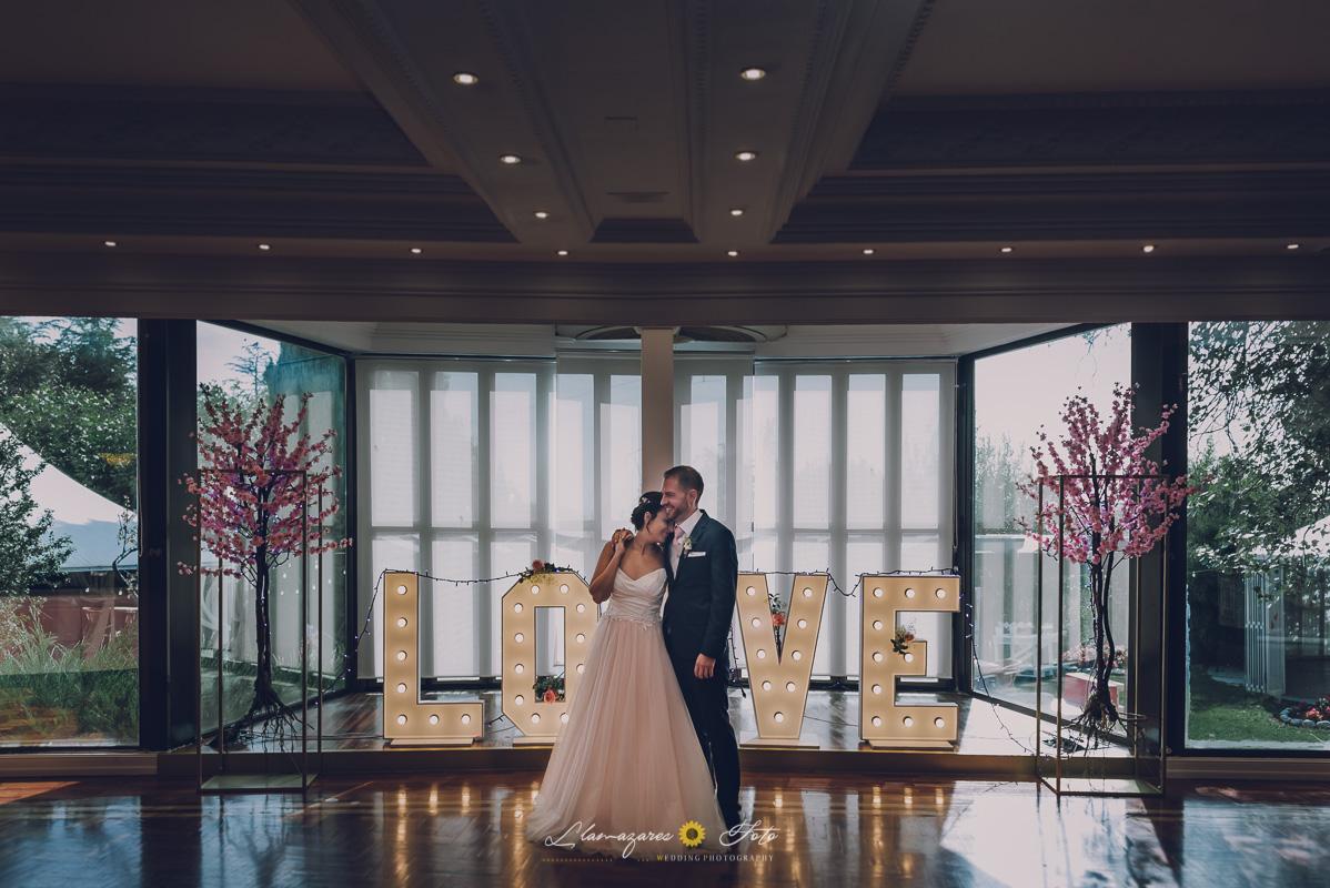 primer baile de pareja en aranda de duero con el vestido rosa de la novia y palabras love iluminadas detras