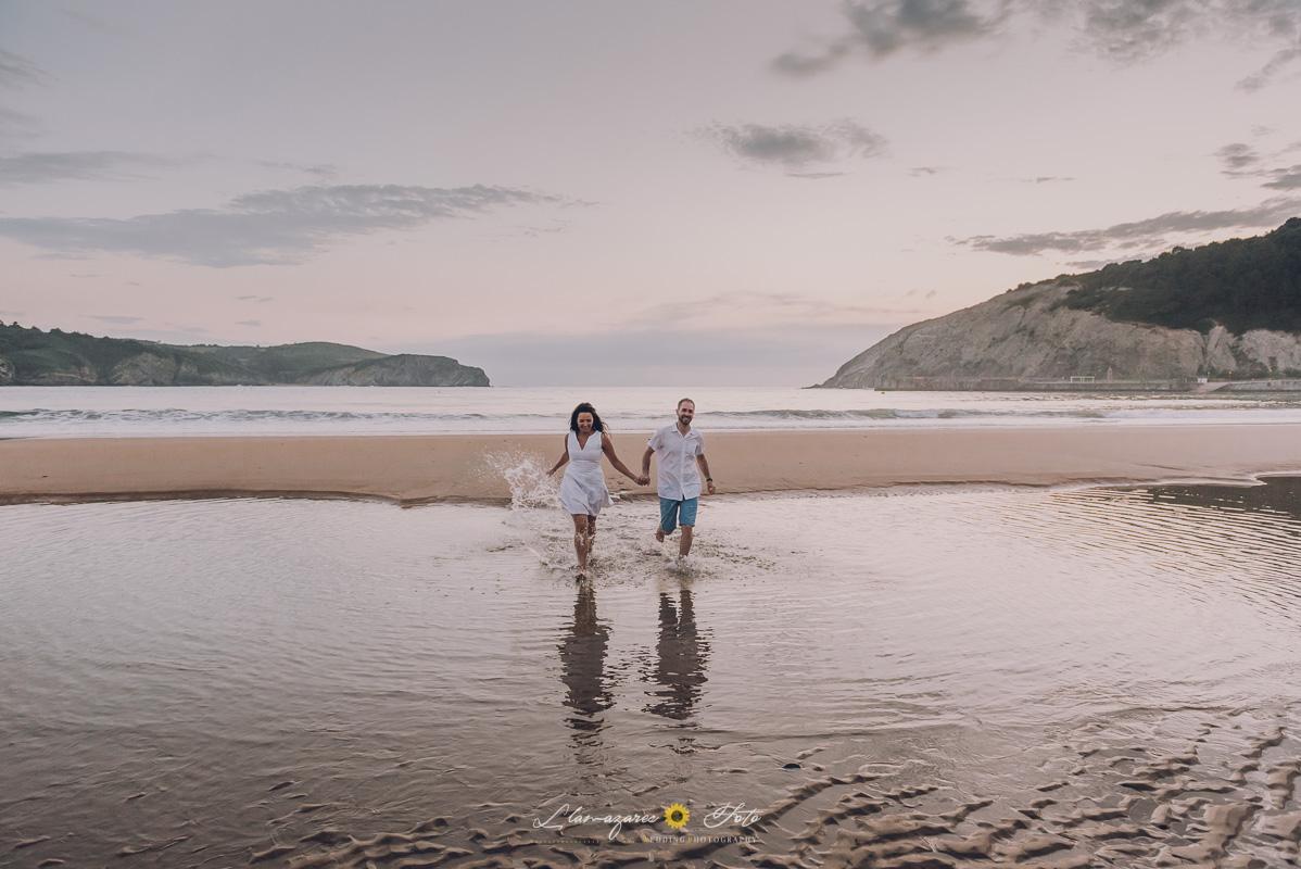 Preboda en la playa. Novios corriendo sobre el agua