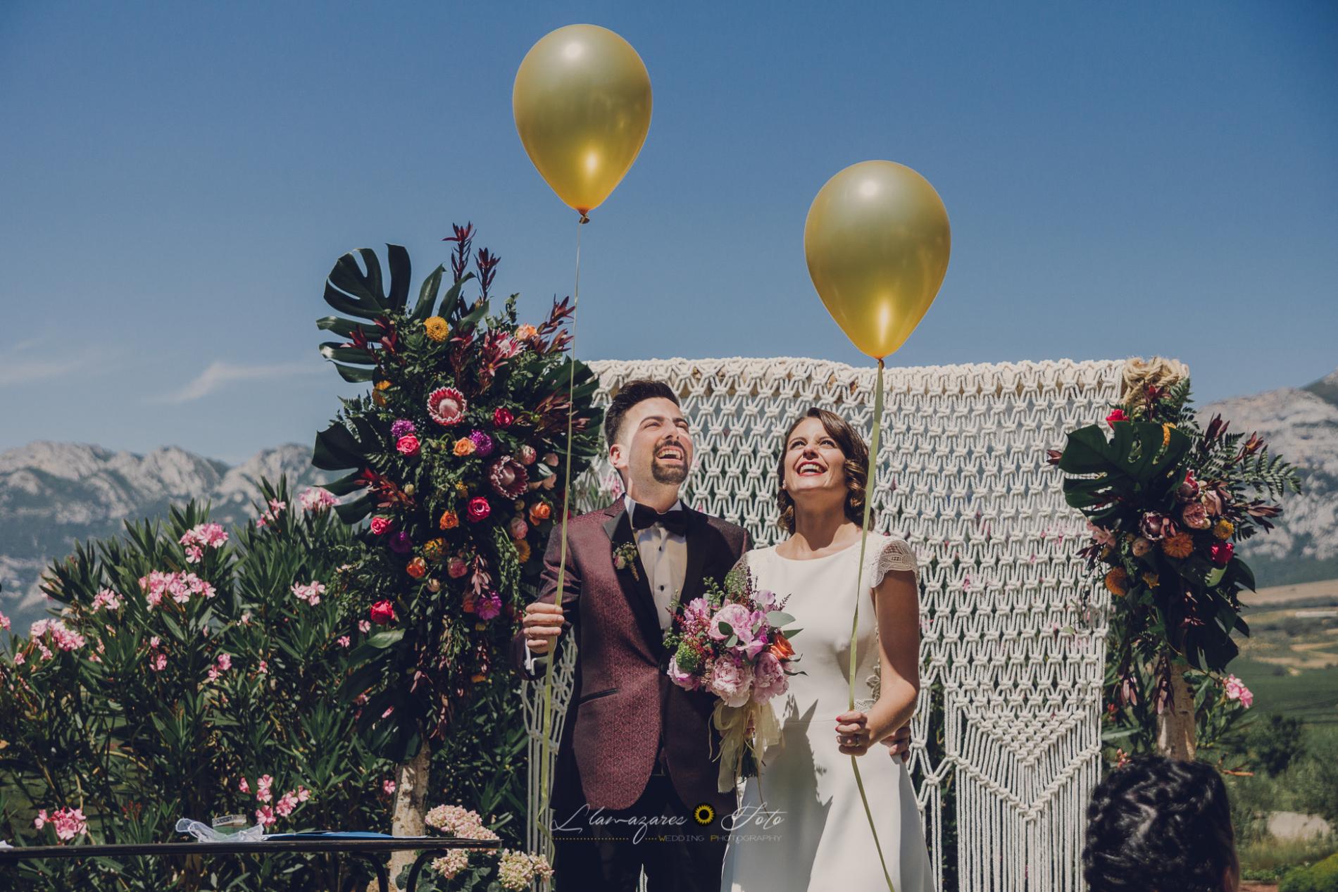Novios millennials haciendo una suelta de globos en su ceremonia